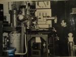 1965 г. А.Г. Коваль (ст. научн. сотр., к. ф.-м. н., центральный корпус ХГУ им. А.М. Горького, пл. Дзержинского, 4) возле установки по изучению оптических спектров излучения при взаимодействии быстрых электронов с молекулами атмосферных газов. В 1964 г. в лаборатории ионных процессов начинает работать старший научный сотрудник А.Г. Коваль. Он совместно с аспирантом В.Т. Коппе, инженером П.А. Брауде и студентами (Н.П. Данилевский, Р.Ф. Котляр и др.) создает две установки по изучению взаимодействий быстрых электронов с молекулами разреженных газов. С этих установок начинается цикл работ по исследованию спектров свечения молекулярных газов и измерению абсолютных сечений возбуждения молекул быстрыми электронами. В 1972-2002 г.г. А.Г.Коваль заведовал ПНИЛ ИП. При этом неоднократно был отмечен вклад её коллектива в эффективную связь науки с производством